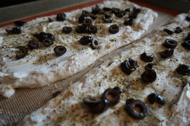 Layer cream cheese, seasonings and olives on dough.